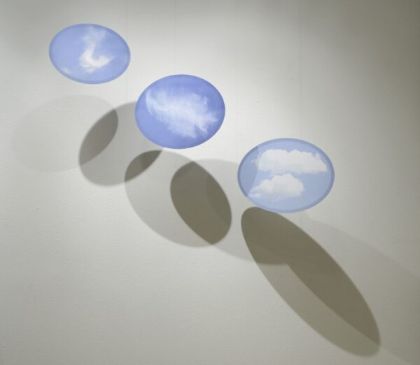 Three Clouds (2016), pigmented inkjet print, steel, and monofilament, 27 x 42 x 16 in. (suspended)