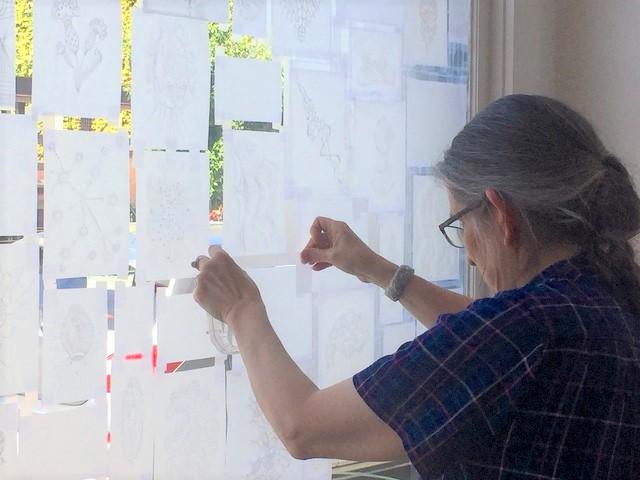 Andrea installing her window exhibit July 2020
